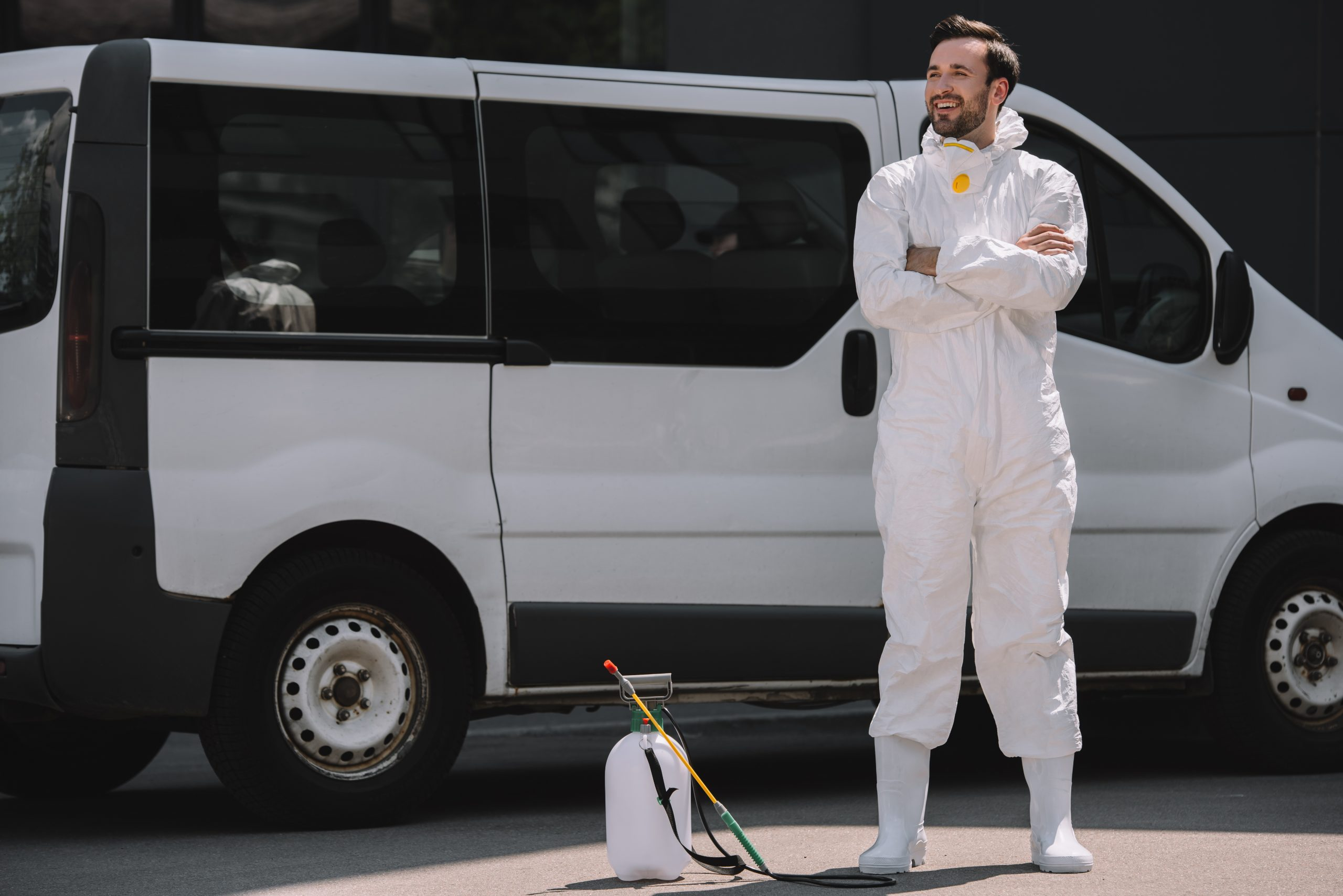smiling pest control worker in uniform standing with crossed arms near car and sprayer on street